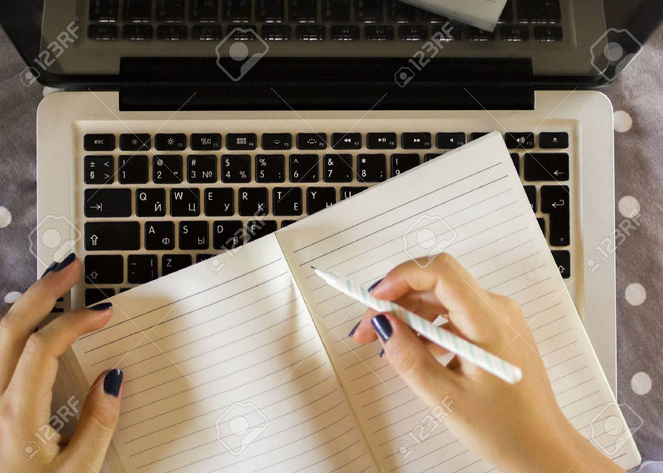43490083-girl-writes-in-a-notebook-with-laptop